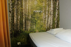 Bed with a forest decorated wall in Yess hotel Kristiansand